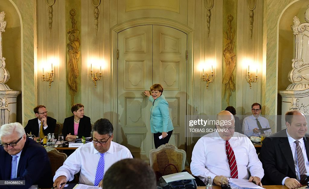 German Chancellor Angela Merkel (C) arrives for the weekly cabinet meeting taking place in the framework of a retreat meeting of the German cabinet at Meseberg Palace on May 25, 2016 in Meseberg near Gransee, northeastern Germany. / AFP / TOBIAS