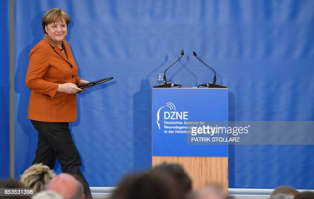 German Chancellor Angela Merkel arrives on stage prior a speech during her visit at the Research Center for Neurodegenerative Diseases on March 15...
