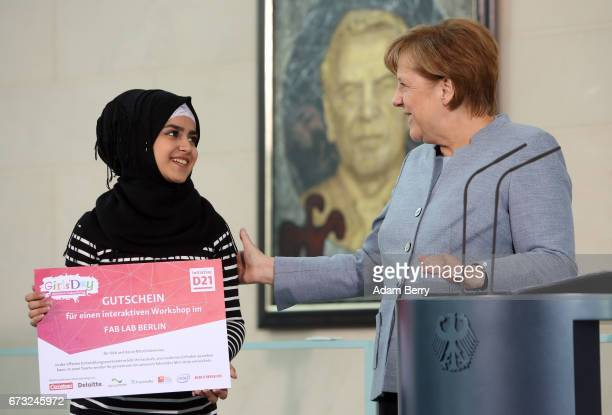 German Chancellor Angela Merkel awards participant Sedra Al Muntaha Mustafa in Germany from Syria for year and a half a certificate for winning a...