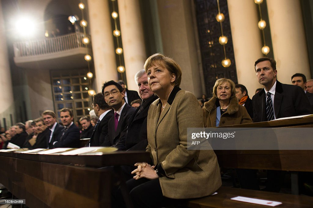 German Chancellor Angela Merkel, Bavaria's State Premier Horst Seehofer, German Economy Minister and vice-chancellor Philipp Roesler and German Interior Minister Hans-Peter Friedrich attend a mass service to mark the resignation of Pope Benedict XVI at the St. Hedwig's Cathedral in Berlin on February 28, 2013. The mass coincides with the final hour of Benedict XVI papacy as his powers formally expire at 19:00 GMT.