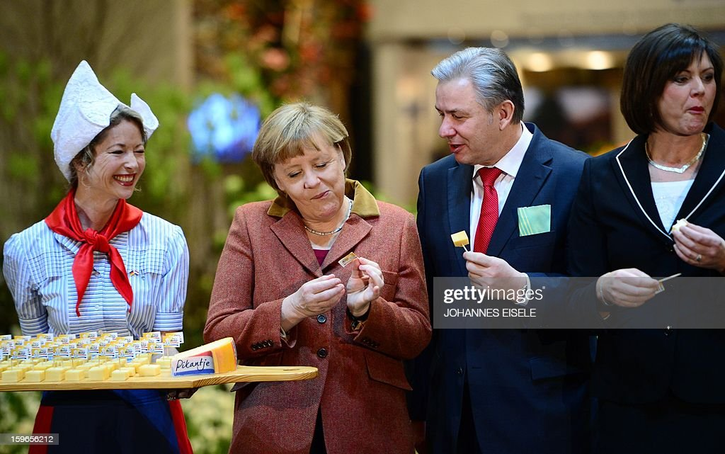German Chancellor Angela Merkel (2ndL), Berlin Mayor Klaus Wowereit (2ndR) and German Agriculture Minister Ilse Aigner (R) taste Dutch cheese at the Netherlands' booth during the opening of the Gruene Woche (Green Week) Agricultural Fair in Berlin on January 18, 2013. This year the official partner country of the fair is The Netherlands.