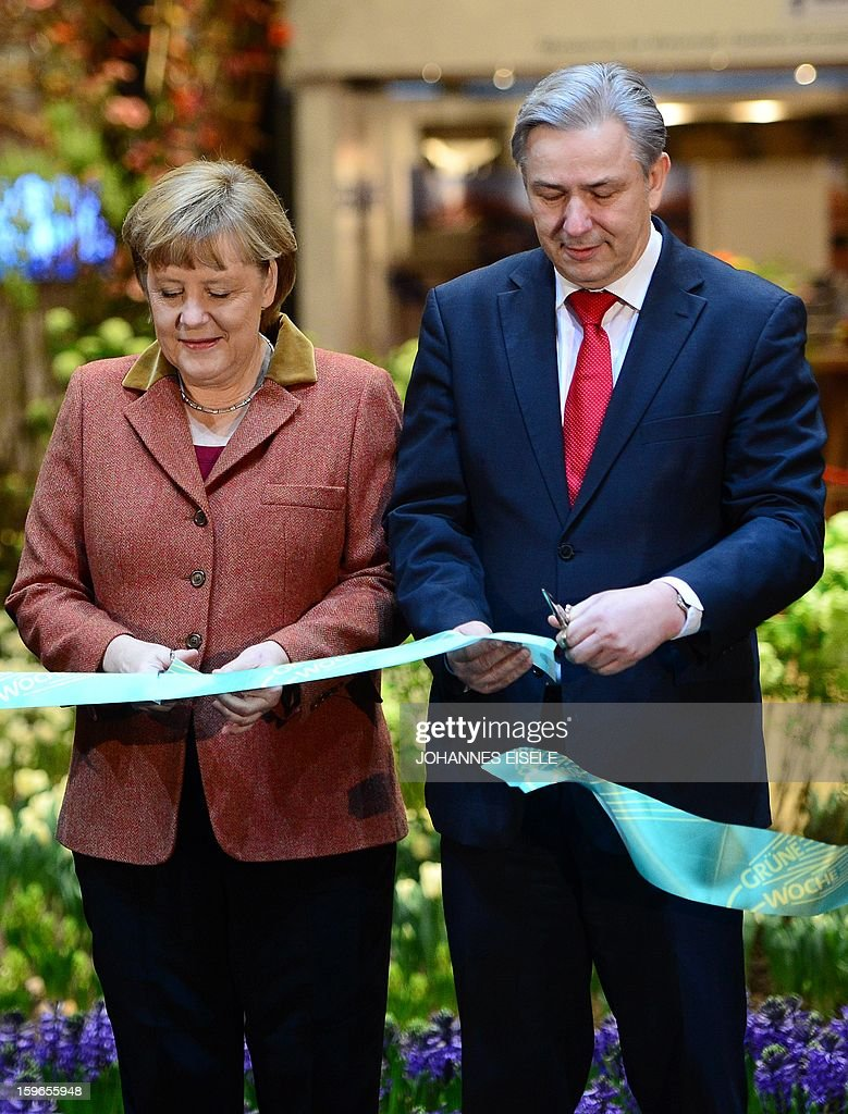 German Chancellor Angela Merkel, Berlin Mayor Klaus Wowereit (R) cut a ribbon on January 18, 2013 during the opening of the Green Week Agricultural Fair in Berlin.