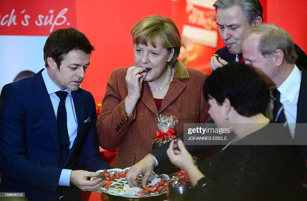 German Chancellor Angela Merkel (2ndL), Berlin Mayor Klaus Wowereit (3rdL) taste chocolate during the opening of the Gruene Woche (Green Week) Agricultural Fair in Berlin on January 18, 2013. This year the official partner country of the fair is The Netherlands. AFP PHOTO / JOHANNES EISELE