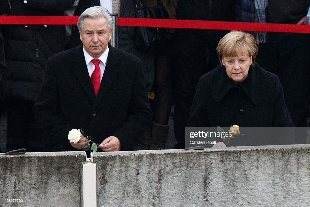 German Chancellor Angela Merkel Berlin's Major Klaus Wowereit and other dignitaries place flowers in between slats of the former Berlin Wall at the...