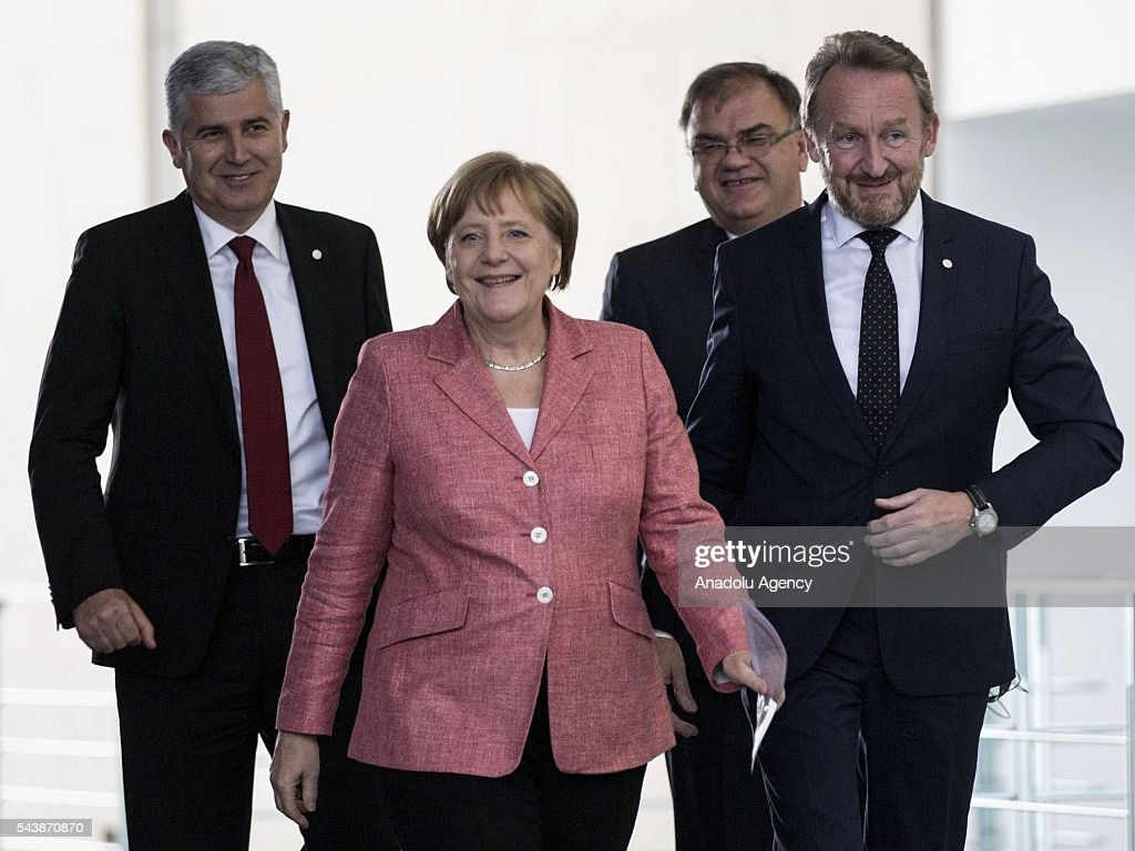 German Chancellor Angela Merkel (2nd L) Bosniak Member of the Presidency of Bosnia and Herzegovina Bakir Izetbegovic (R), Serbian Member of the Presidency of Bosnia and Herzegovina Mladen Ivanic (2nd R) and Croat Member of the Presidency of Bosnia and Herzegovina Dragan Covic (L) arrive for a press conference following their meeting at the Federal Chancellery in Berlin, Germany on June 30, 2016.