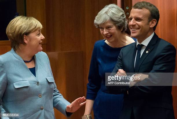 German Chancellor Angela Merkel Britain Prime minister Theresa May and French President Emmanuel Macron talk as they arrive in Brussels on October 19...