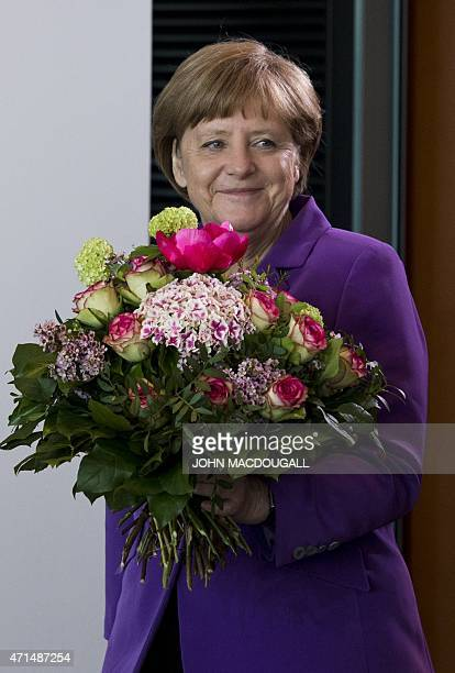 German Chancellor Angela Merkel carries a bouquet for the German Environment Minister on the occasion of her birthday during a weekly meeting of the...