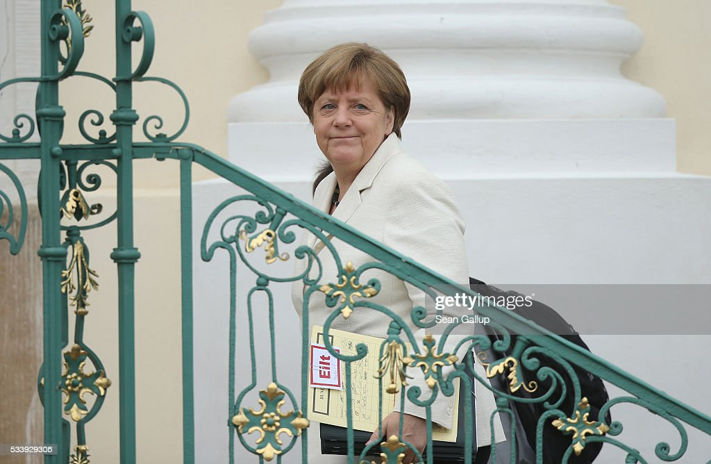 German Chancellor <a gi-track='captionPersonalityLinkClicked' href=/galleries/search?phrase=Angela+Merkel&family=editorial&specificpeople=202161 ng-click='$event.stopPropagation()'>Angela Merkel</a> carries a folder with red text that reads: 'urgent' as she arrives for a meeting of the German government cabinet together with European Commissioner for Energy in the European Commission Guenther Oettinger at Schloss Meseberg palace on May 24, 2016 in Gransee, Germany. The government cabinet is meeting at Schloss Meseberg for a two-day retreat.