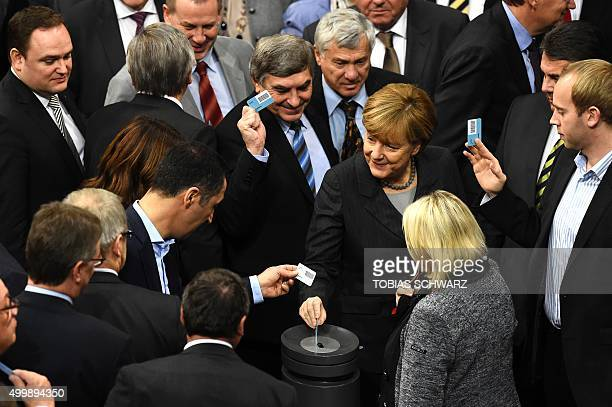 German Chancellor Angela Merkel casts her ballot after a plenary session of the German lower house of parliament Bundestag as deputies vote on a...