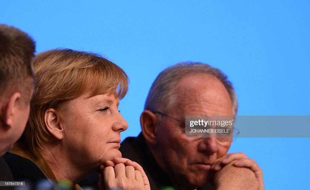 German Chancellor Angela Merkel, CDU Secretary General Hermann Groehe (L) and German Finance Minister Wolfgang Schaeuble (R) attend a congress of Germany's ruling conservative Christian Democratic Union (CDU) party on December 4, 2012 in Hanover, central Germany. German Chancellor Angela Merkel was re-elected head of her conservative Christian Democrats (CDU) by more than 97 percent of delegates' votes at a two-day party congress. It was Merkel's best result since she took over as chairman of the CDU in 2000 and comes as she gears up for fighting for a third term at the helm of Europe's top economy in elections expected in September 2013. AFP PHOTO / JOHANNES EISELE