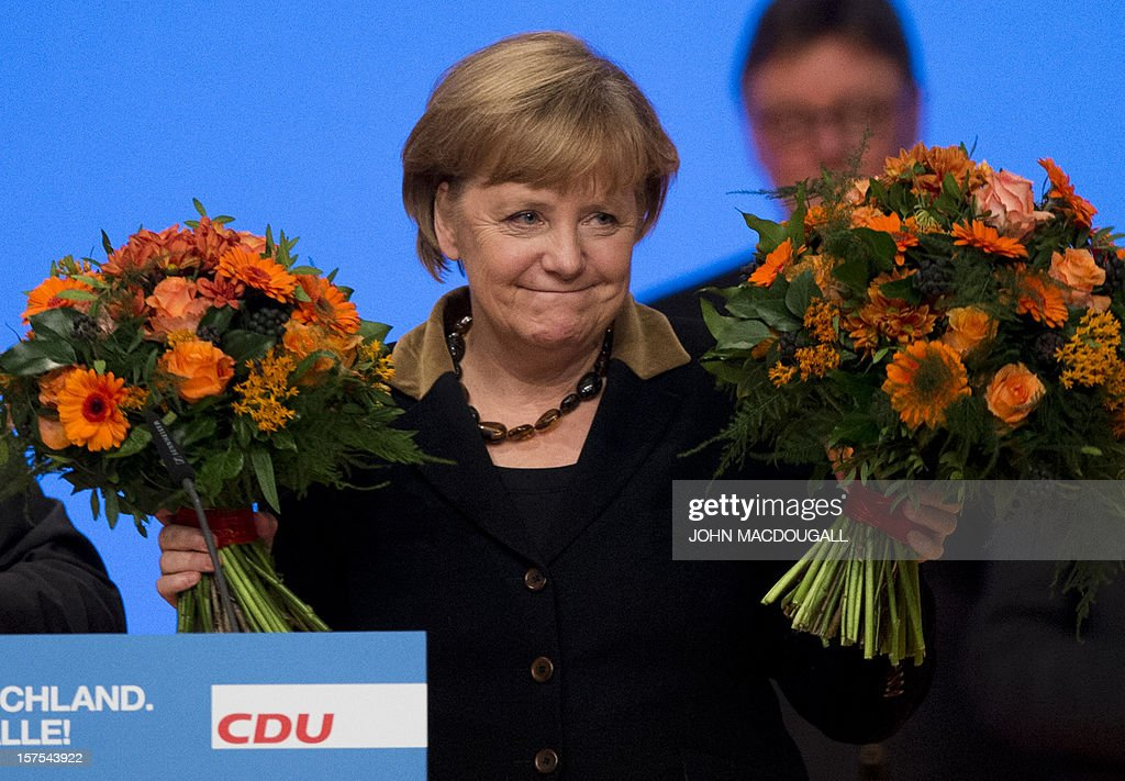 German Chancellor Angela Merkel celebrates after she was re-elected head of her party during a congress of Germany's ruling conservative Christian Democratic Union (CDU) party on December 4, 2012 in Hanover, central Germany. German Chancellor Angela Merkel was re-elected head of her conservative Christian Democrats (CDU) by more than 97 percent of delegates' votes at a two-day party congress. It was Merkel's best result since she took over as chairman of the CDU in 2000 and comes as she gears up for fighting for a third term at the helm of Europe's top economy in elections expected in September 2013.