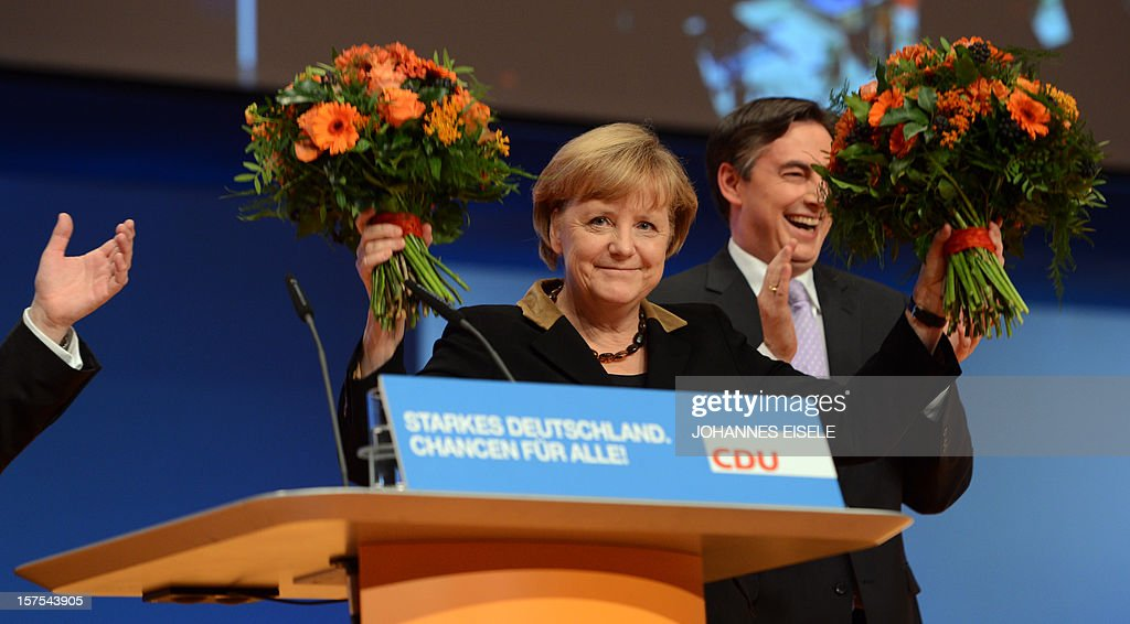 German Chancellor Angela Merkel celebrates with Lower Saxony's State Premier David McAllister (R) after she was re-elected head of her party during a congress of Germany's ruling conservative Christian Democratic Union (CDU) party on December 4, 2012 in Hanover, central Germany. German Chancellor Angela Merkel was re-elected head of her conservative Christian Democrats (CDU) by more than 97 percent of delegates' votes at a two-day party congress. It was Merkel's best result since she took over as chairman of the CDU in 2000 and comes as she gears up for fighting for a third term at the helm of Europe's top economy in elections expected in September 2013.