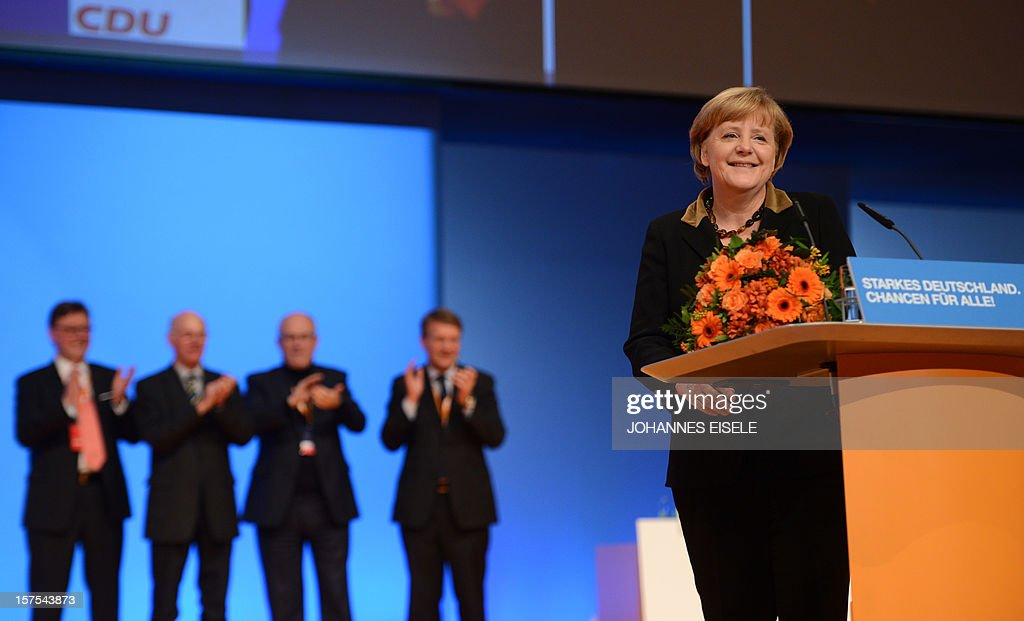 German Chancellor Angela Merkel celebtates after she was re-elected head of her party during a congress of Germany's ruling conservative Christian Democratic Union (CDU) party on December 4, 2012 in Hanover, central Germany. German Chancellor Angela Merkel was re-elected head of her conservative Christian Democrats (CDU) by more than 97 percent of delegates' votes at a two-day party congress. It was Merkel's best result since she took over as chairman of the CDU in 2000 and comes as she gears up for fighting for a third term at the helm of Europe's top economy in elections expected in September 2013.