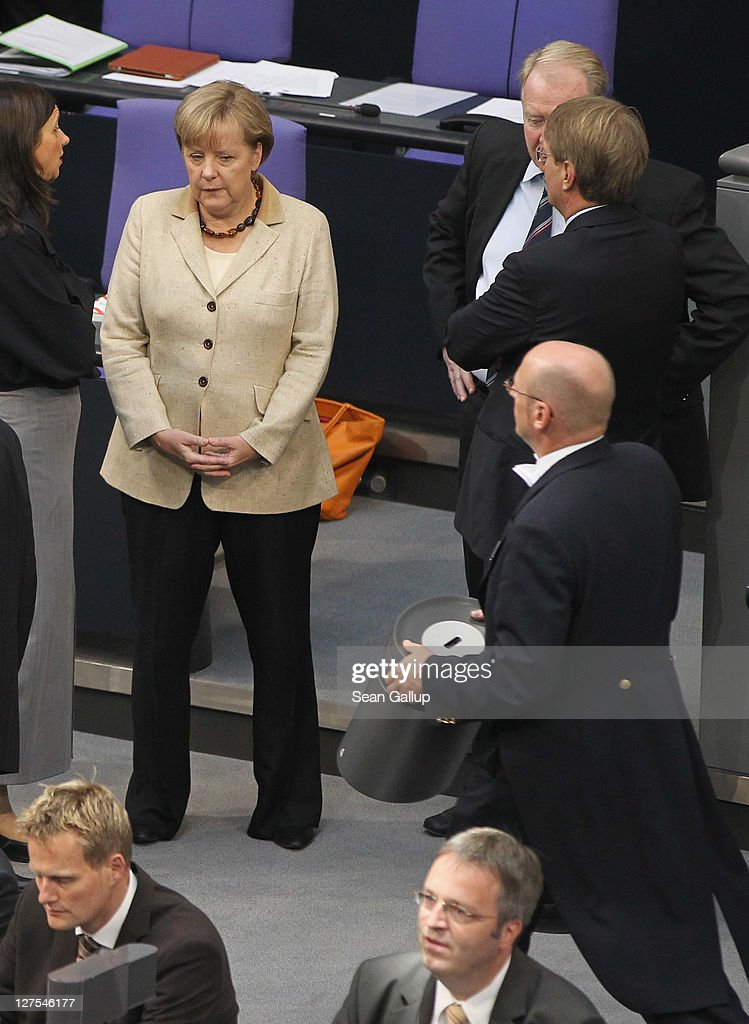 German Chancellor Angela Merkel (L) chats with a colleague as a Bundestag aide carries a ballot box away shortly after Bundestag members voted on an increase in funding for the European Financial Stability Facility (EFSF) on September 29, 2011 in Berlin, Germany. Many analysts see the increase as crucial for safeguarding the future stability of the Euro in the face of the current debt crisis in Greece. Merkel is pressing for the increase, and though opposition parties have pledged to support the bill, up to 19 dissenters within the ranks of her own coalition might vote against it.