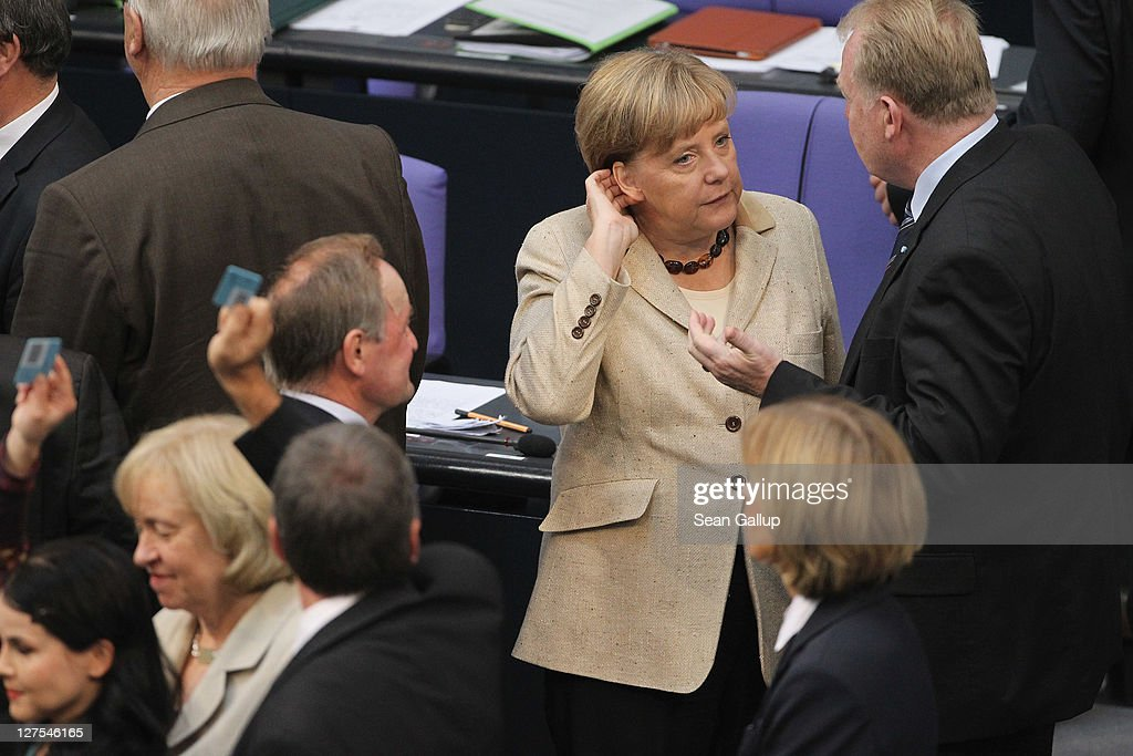German Chancellor Angela Merkel (C) chats with a colleague shortly after casting her ballot along with other Bundestag members in voting on an increase in funding for the European Financial Stability Facility (EFSF) on September 29, 2011 in Berlin, Germany. Many analysts see the increase as crucial for safeguarding the future stability of the Euro in the face of the current debt crisis in Greece. Merkel is pressing for the increase, and though opposition parties have pledged to support the bill, up to 19 dissenters within the ranks of her own coalition might vote against it.