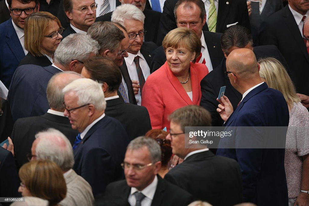 German Chancellor Angela Merkel (in red) chats with colleagues after casting her balot during votes over the third EU financial aid package to Greece at an extraordinary session of the German parliament, the Bundestag, on July 17, 2015 in Berlin, Germany. The Bundestag is among several European parliaments that must vote on whether to allow negotations over the aid package that will help Greece to avert state bankruptcy and shore up the Greek banking system.