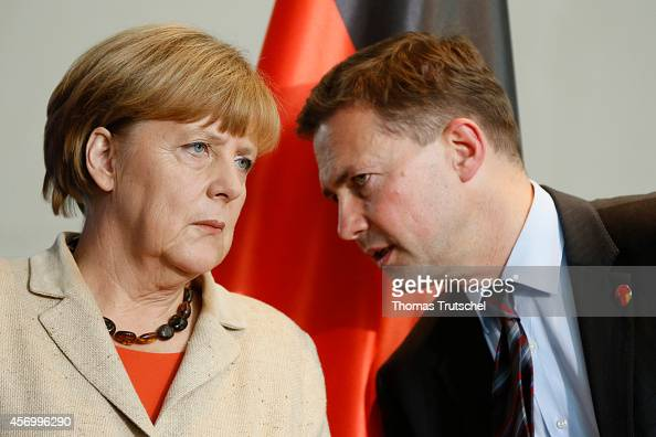 German Chancellor Angela Merkel chats with German government spokesperson Steffen Seibert during a signing ceremony on October 10 2014 in Berlin...