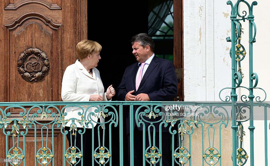 German Chancellor Angela Merkel chats with German Vice Chancellor, Economy and Energy Minister Sigmar Gabriel prior to a closed meeting of the German cabinet at Meseberg Palace on May 24, 2016 in Meseberg, northeastern Germany. / AFP / TOBIAS