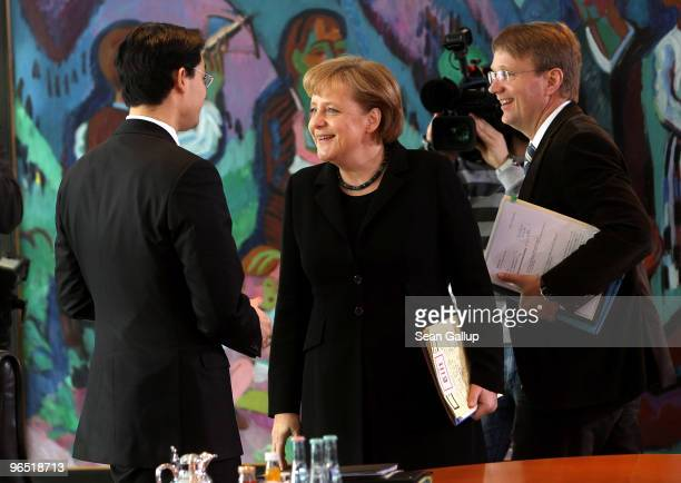 German Chancellor Angela Merkel chats with Health Minister Philipp Roesler as Minister of the Chancellery Ronald Pofalla walks by upon her arrival...