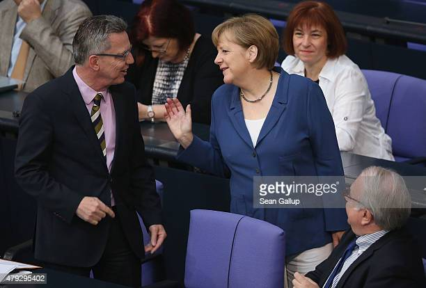 German Chancellor Angela Merkel chats with Interior Minister Thomas de Maiziere as she arrives for a session of the Bundestag on July 3 2015 in...