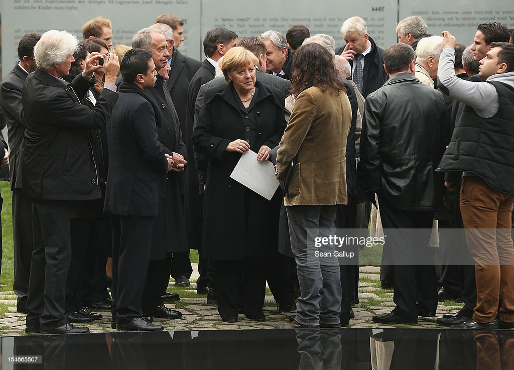 """German Chancellor <a gi-track='captionPersonalityLinkClicked' href=/galleries/search?phrase=Angela+Merkel&family=editorial&specificpeople=202161 ng-click='$event.stopPropagation()'>Angela Merkel</a> (C) chats with mebers of Germany's Roma community at the inauguration of the """"Memorial to the Sinti and Roma of Europe Murdered Under National Socialism"""" on October 24, 2012 in Berlin, Germany. In addition to targeting Jews during the Holocaust, Hitler also sought to exterminate the Roma population in Europe and estimates of the number killed range from 220,000 to 1,500,000."""