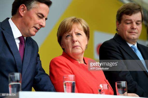 German Chancellor Angela Merkel chats with member of the European Parliament David McAllister during an election campaign event of the Christian...