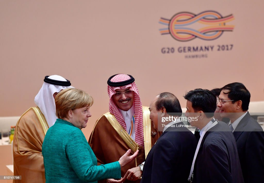 German Chancellor Angela Merkel chats with members of the Saudi and Asian-Pacific Economic Cooperation delegations at the morning working session on the second day of the G20 economic summit on July 8, 2017 in Hamburg, Germany. G20 leaders have reportedly agreed on trade policy for their summit statement but disagree over climate change policy.