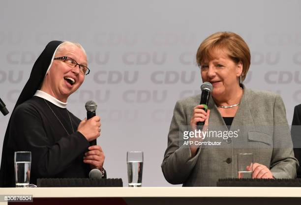 German Chancellor Angela Merkel chats with nun Magaretha during an election campaign event of the Christian Democratic Union party in Dortmund...