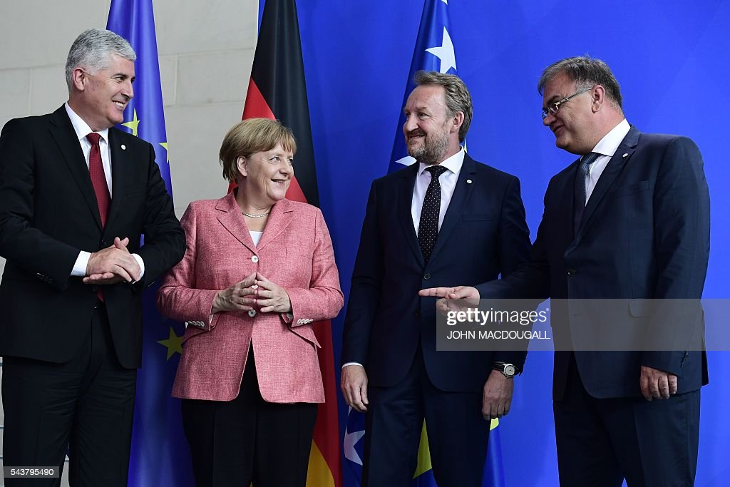 German Chancellor Angela Merkel (2nd L) chats with the three members of the Presidency of Bosnia and Herzegovina Bakir Izetbegovic (2nd R), Dragan Covic (L) and Mladen Ivanic, while posing for the media after a joint press conference at the chancellery in Berlin on June 30, 2016. / AFP / John MACDOUGALL