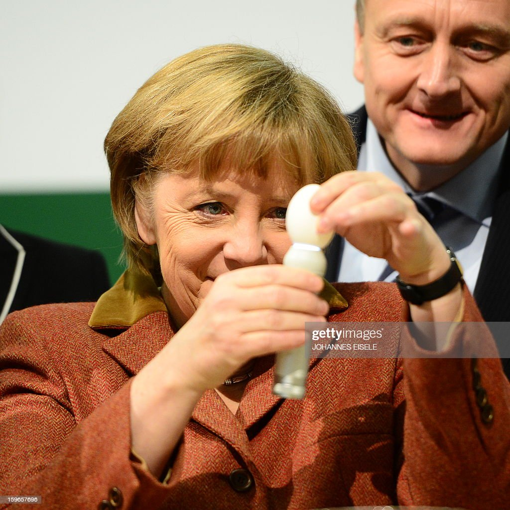 German Chancellor Angela Merkel (C) checks the quality of an egg next to Berlin Mayor Klaus Wowereit (L) at booth as she opens the Gruene Woche Agricultural Fair in Berlin on January 18, 2013. This year the official partner country of the fair is The Netherlands. EISELE