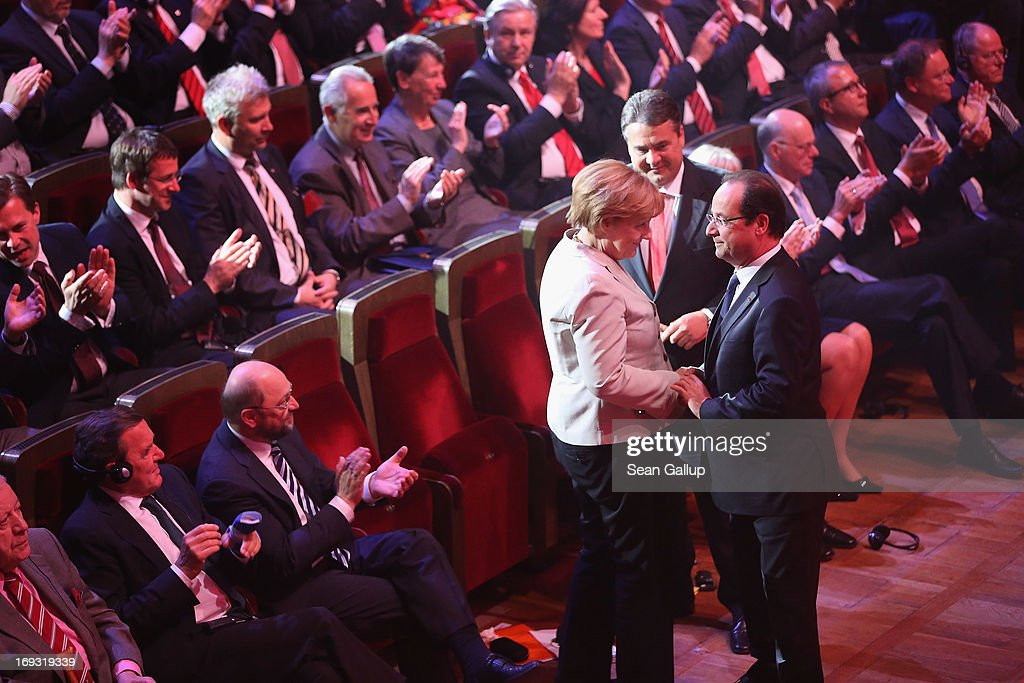 German Chancellor <a gi-track='captionPersonalityLinkClicked' href=/galleries/search?phrase=Angela+Merkel&family=editorial&specificpeople=202161 ng-click='$event.stopPropagation()'>Angela Merkel</a> congratulates French President Francois Hollande after he spoke at the 150th anniversary celebration of the German Social Democrats (SPD) as SPD Chairman <a gi-track='captionPersonalityLinkClicked' href=/galleries/search?phrase=Sigmar+Gabriel&family=editorial&specificpeople=543927 ng-click='$event.stopPropagation()'>Sigmar Gabriel</a> (behind) looks on on May 23, 2013 in Leipzig, Germany. The SPD, Germany's main left-wing party, traces its history to the founding of the 'Allgemeine Deutsche Arbeiterverein' (General German Workers' Association) in Leipzig in May of 1863.