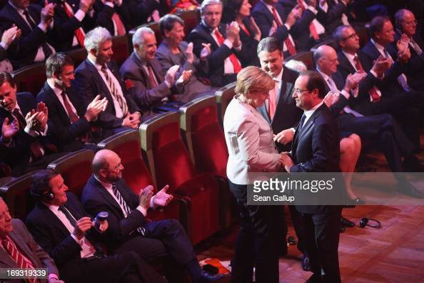 German Chancellor Angela Merkel congratulates French President Francois Hollande after he spoke at the 150th anniversary celebration of the German...