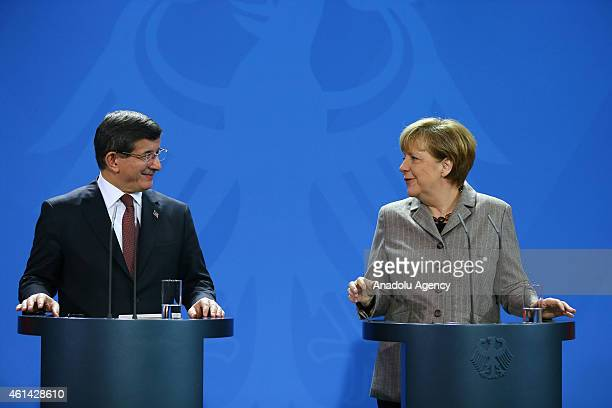 German Chancellor Angela Merkel delivers a speech as Turkish Prime Minister Ahmet Davutoglu listens to her during a joint press conference held after...