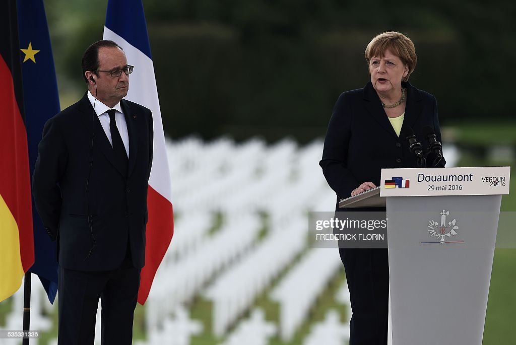 German Chancellor Angela Merkel (R) delivers a speech next to French President Francois Hollande (L) during a remembrance ceremony to mark the centenary of the battle of Verdun, at the Douaumont Ossuary (Ossuaire de Douaumont), northeastern France, on May 29, 2016. The battle of Verdun, in 1916, was one of the bloodiest episodes of World War I. The offensive which lasted 300 days claimed more than 300,000 lives. / AFP / FREDERICK