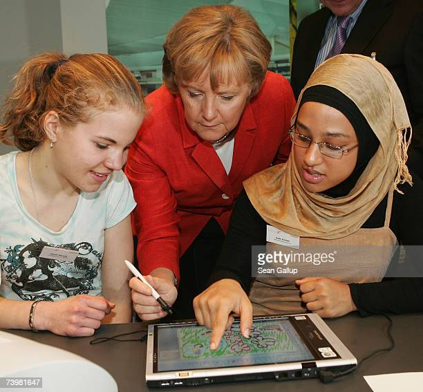 German Chancellor Angela Merkel draws with an electronic pen on a digital tablet with students Natalie Michalik and Nadin ElSaleh of Breitscheid...