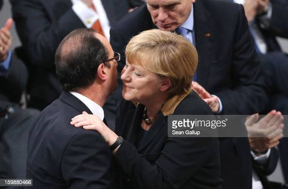 German Chancellor Angela Merkel embraces French President Francois Hollande after she spoke to members of the German Bundestag and French Assemblee...