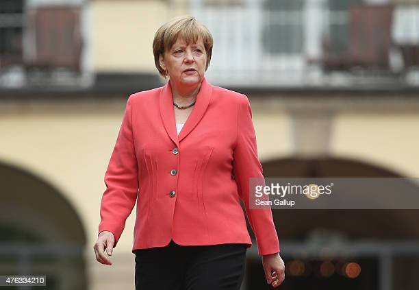 German Chancellor Angela Merkel emerges to greet guests of the Outreach program on the second day of the summit of G7 nations at Schloss Elmau on...