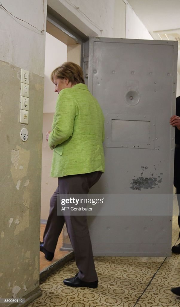 German Chancellor Angela Merkel enters a cell as she visits the Berlin-Hohenschönhausen Memorial at the site of a former prison of the East German Ministry of State Security (MfS; 'Stasi') in Berlin on August 11, 2017. Thousands of political prisoners passed through this jail, including nearly all the prominent figures who opposed the regime of the German Democratic Republic (GDR). / AFP PHOTO / POOL / Wolfgang Kumm