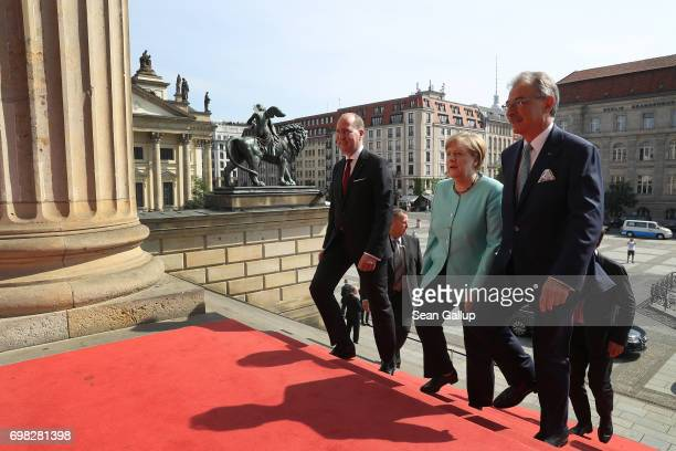 German Chancellor Angela Merkel flanked by BDI Director Joachim Lang and BDI President Dieter Kempf arrives to speak at the annual congress of the...