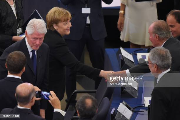 German Chancellor Angela Merkel flanked by US former President Bill Clinton shakes hands as sh arrives at the European Parliament in Strasbourg...