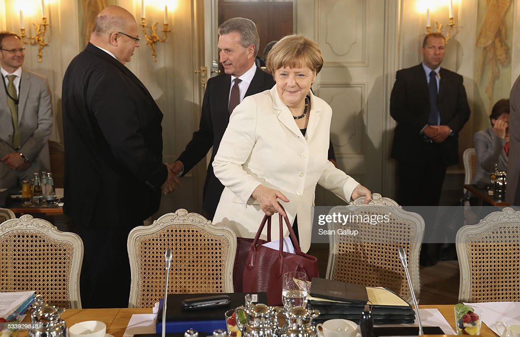 German Chancellor <a gi-track='captionPersonalityLinkClicked' href=/galleries/search?phrase=Angela+Merkel&family=editorial&specificpeople=202161 ng-click='$event.stopPropagation()'>Angela Merkel</a> (C), followed by European Commissioner for Digital Economy and Society Guenther Oettinger, arrives for a meeting of the German government cabinet at Schloss Meseberg palace on May 24, 2016 in Gransee, Germany. The government cabinet is meeting at Schloss Meseberg for a two-day retreat.