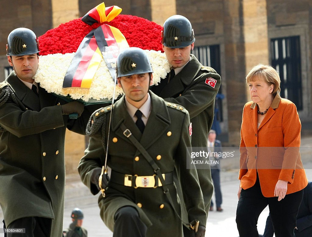 German Chancellor Angela Merkel (R) follows an honour guard as she visits the mausoleum of Turkey's Republic's founder Kemal Ataturk in Ankara, on February 25, 2013, on the second an final day of her official visit to Turkey.