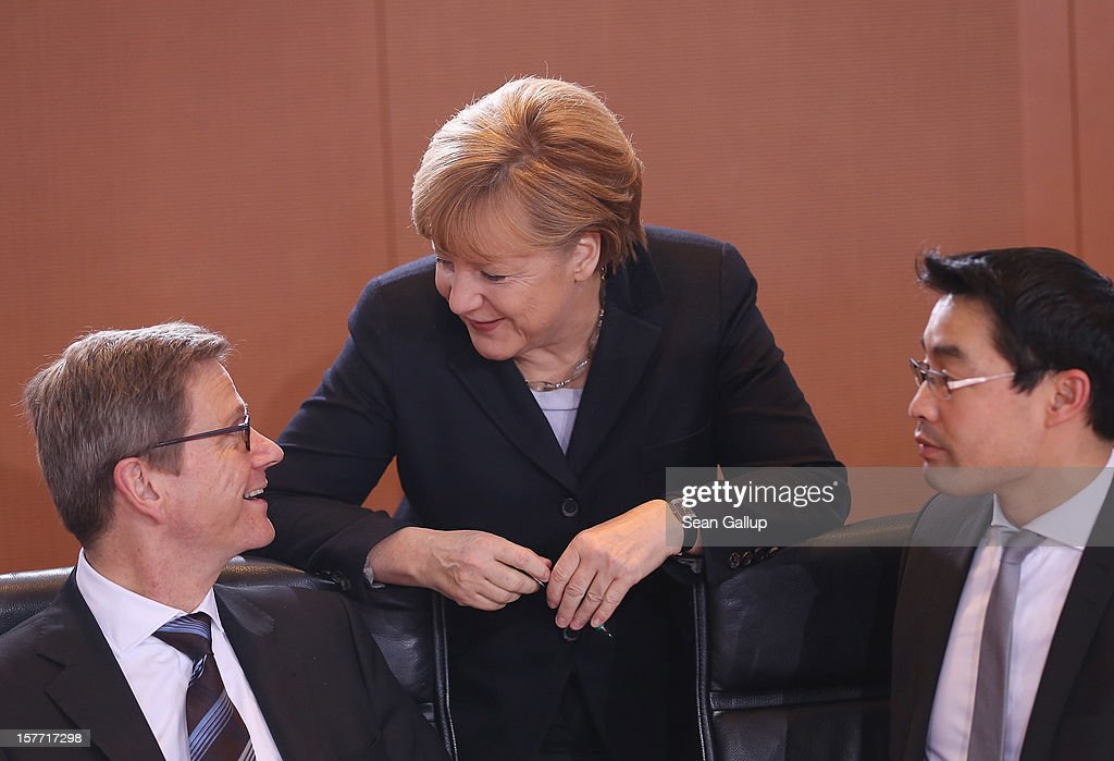 German Chancellor Angela Merkel, Foreign Minister <a gi-track='captionPersonalityLinkClicked' href=/galleries/search?phrase=Guido+Westerwelle&family=editorial&specificpeople=208748 ng-click='$event.stopPropagation()'>Guido Westerwelle</a> (L) and Vice Chancellor and Economy Minister Philipp Roesler arrive for the weekly German government cabinet meeting on December 6, 2012 in Berlin, Germany. The German and Israeli governments are meeting later in the day for German-Israeli government consultations.
