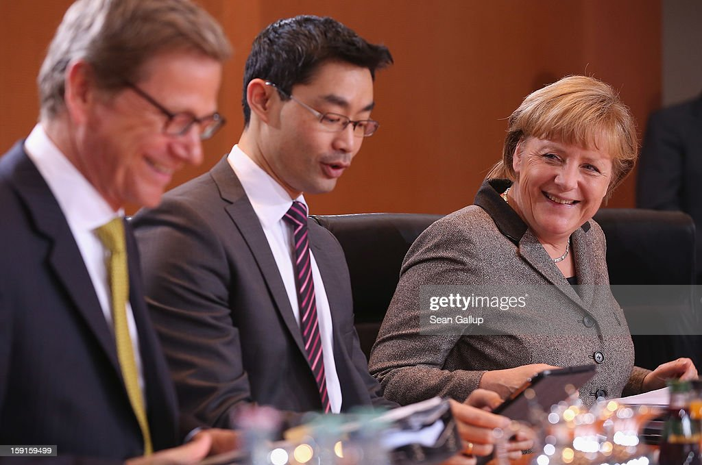German Chancellor <a gi-track='captionPersonalityLinkClicked' href=/galleries/search?phrase=Angela+Merkel&family=editorial&specificpeople=202161 ng-click='$event.stopPropagation()'>Angela Merkel</a> (R), Foreign Minister <a gi-track='captionPersonalityLinkClicked' href=/galleries/search?phrase=Guido+Westerwelle&family=editorial&specificpeople=208748 ng-click='$event.stopPropagation()'>Guido Westerwelle</a> (L) and Vice Chancellor and Economy Minister Philipp Roesler arrive for the weekly German government cabinet meeting on January 9, 2013 in Berlin, Germany. High on the morning's agenda was the latest government culture and education report.