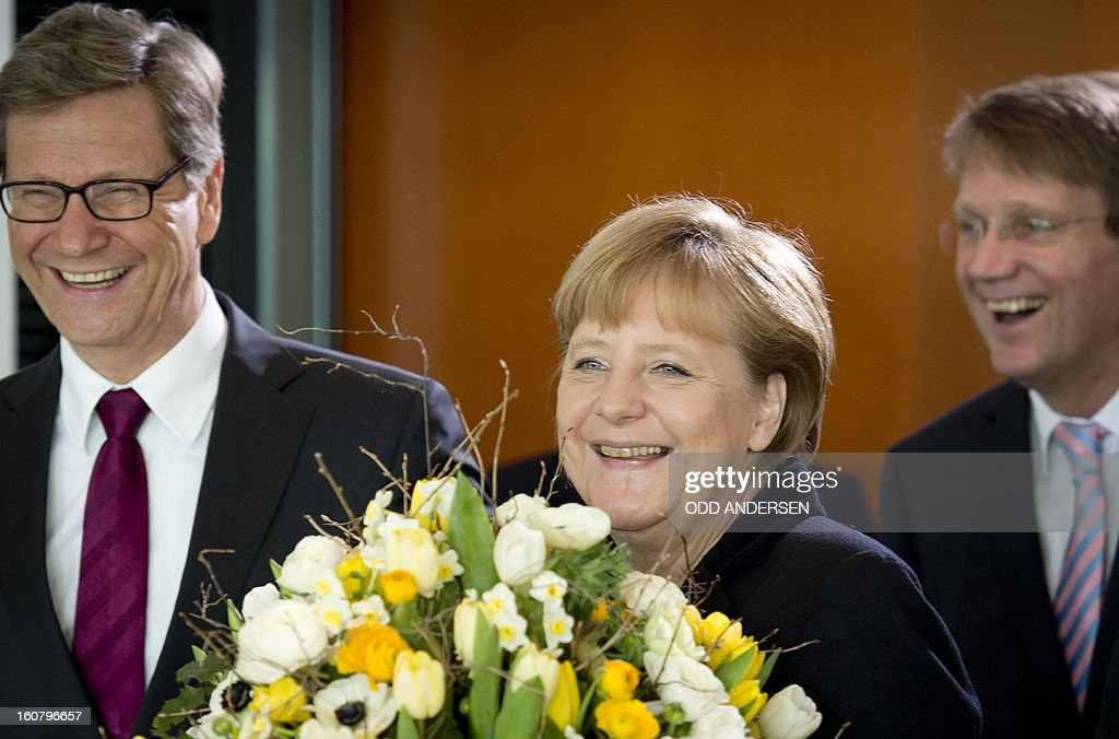 German Chancellor Angela Merkel (C), foreign minister Guido Westerwelle (L) and chief of staff Roland Pofalla (R) present a staff member with flowers on his 50th birthday during the weekly cabinet meeting at the Chancellery in Berlin on February 6, 2013.