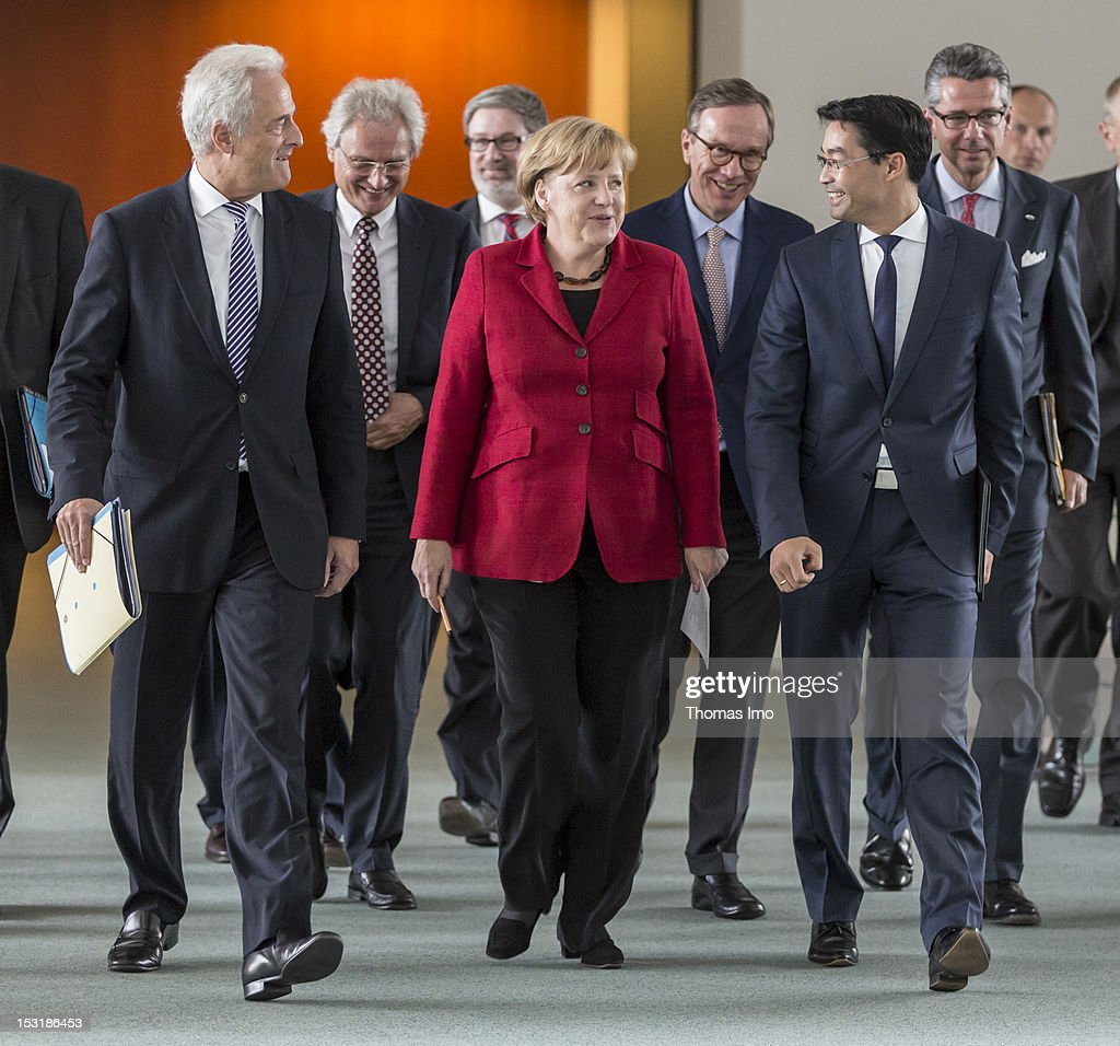 German Chancellor <a gi-track='captionPersonalityLinkClicked' href=/galleries/search?phrase=Angela+Merkel&family=editorial&specificpeople=202161 ng-click='$event.stopPropagation()'>Angela Merkel</a> (C) German Transport Minister <a gi-track='captionPersonalityLinkClicked' href=/galleries/search?phrase=Peter+Ramsauer&family=editorial&specificpeople=770626 ng-click='$event.stopPropagation()'>Peter Ramsauer</a> (L) German Economy Minister and Vice Chancellor Philipp Roesler (R), the second row (L-R): Prof. Dr. Henning Kagermann, President Deutsche Akademie der Technikwissenschaften; Economic Advisor Prof. Dr. Lars Hendrik Roeller, Matthias Wissmann, President Verband der Automobilindustrie, VDA, and Ulrich Grillo, Vice President of the Voice of German Industry, BDI, on the way to the press conference after the meeting for the federal government's national development plan for electric mobility on October 1, 2012 in Berlin, Germany. It has been reported that the German government is to scrap it's target of having one million electric cars on the roads by 2020.