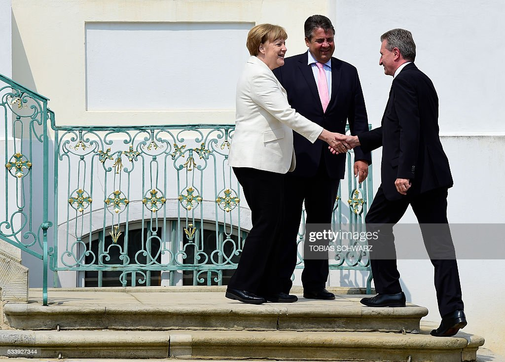 German Chancellor Angela Merkel, German Vice Chancellor, Economy and Energy Minister Sigmar Gabriel and the European Commissioner for Energy in the European Commission Günther Oettinger talk prior to a closed meeting of the German cabinet at Meseberg Palace on May 24, 2016 in Meseberg, northeastern Germany. / AFP / TOBIAS