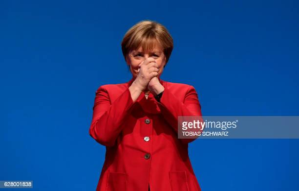 TOPSHOT German Chancellor Angela Merkel gestures after addressing delegates during her conservative Christian Democratic Union party's congress in...