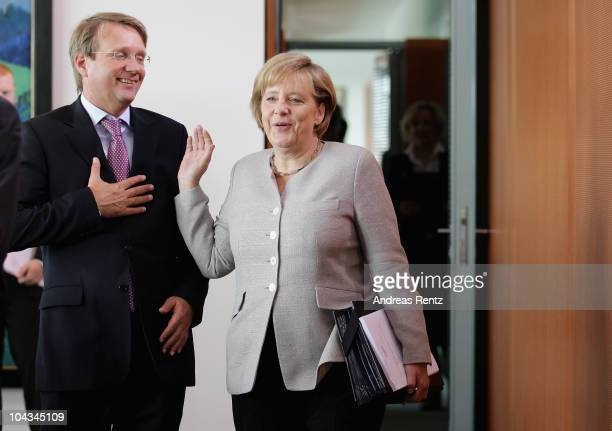 German Chancellor Angela Merkel gestures as Minister of the Chancellery Ronald Pofalla smiles upon their arrival the weekly German government cabinet...