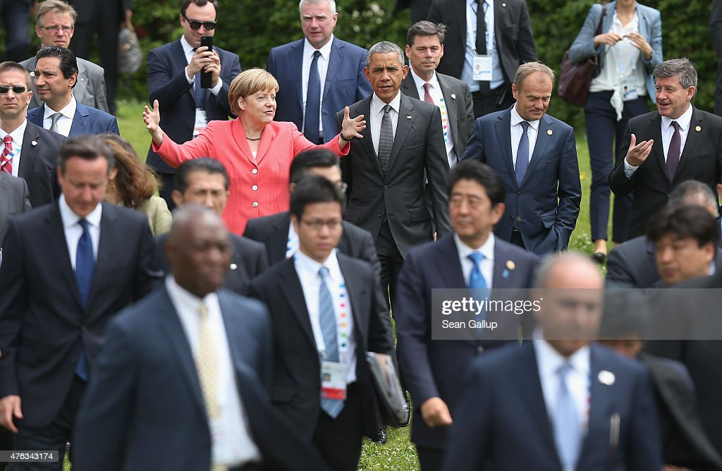 German Chancellor <a gi-track='captionPersonalityLinkClicked' href=/galleries/search?phrase=Angela+Merkel&family=editorial&specificpeople=202161 ng-click='$event.stopPropagation()'>Angela Merkel</a> (in pink) gestures as she, U.S. President <a gi-track='captionPersonalityLinkClicked' href=/galleries/search?phrase=Barack+Obama&family=editorial&specificpeople=203260 ng-click='$event.stopPropagation()'>Barack Obama</a> (R of her), G7 nation leaders, European Union leaders and Outreach program nation leaders arrive for the Outreach group photo on the second day of the summit of G7 nations at Schloss Elmau on June 8, 2015 near Garmisch-Partenkirchen, Germany. In the course of the two-day summit G7 leaders are scheduled to discuss global economic and security issues, as well as pressing global health-related issues, including antibiotics-resistant bacteria and Ebola.